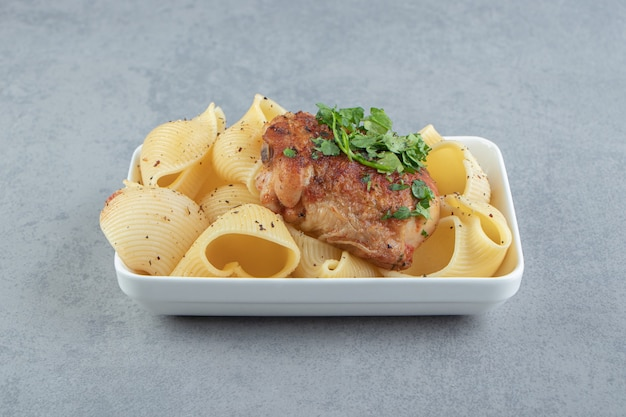 Pasta conchiglie y pollo asado en la placa blanca.