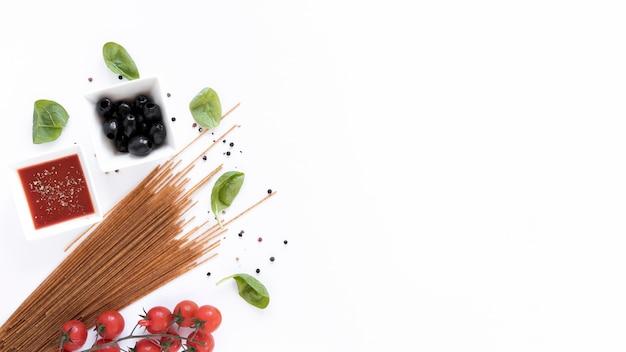 La pasta cruda del espagueti y sus ingredientes para la preparación aislada en la superficie blanca