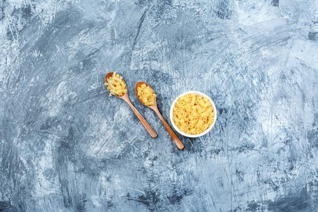 Pasta cruda laicos plana en un tazón y cucharas de madera sobre fondo de yeso sucio. horizontal
