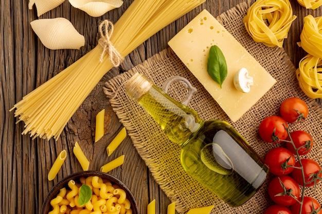 Pasta cruda mezclada con tomates aceite de oliva y queso duro