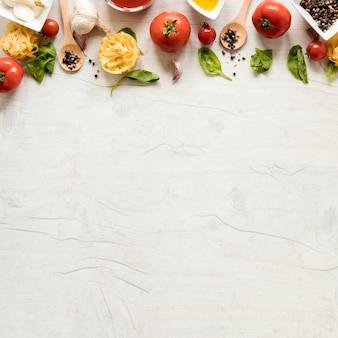 Pasta cruda y sus ingredientes dispuestos en fila sobre mesa de madera blanca