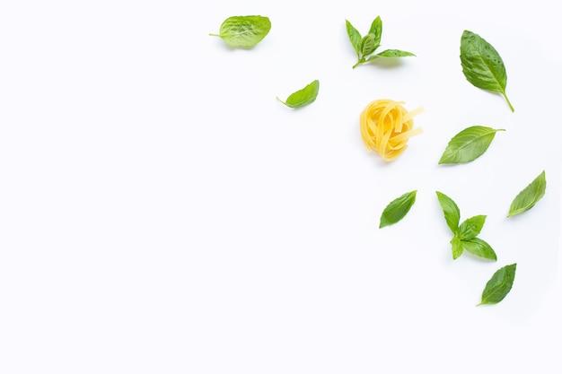 Pasta cruda de tagliatelle con hojas de albahaca