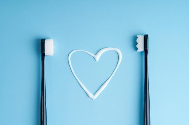 Pasta de dientes en forma de corazón entre dos cepillos de dientes.