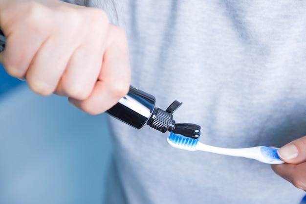 Pasta de dientes pasta negra hecha de carbón activado en un cepillo,