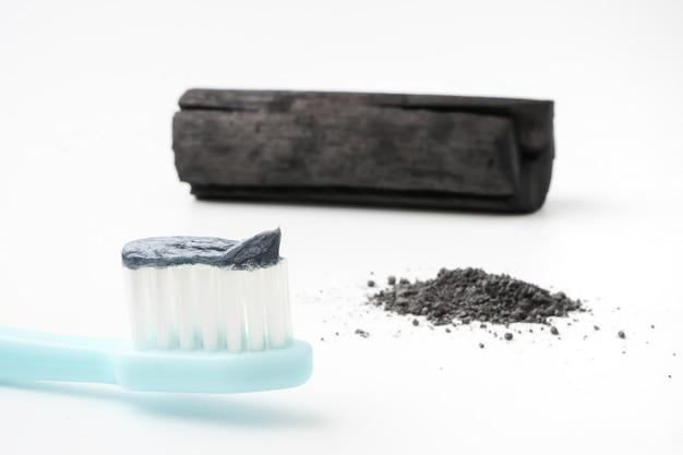 Pasta de dientes por polvo de carbón activado sobre fondo blanco