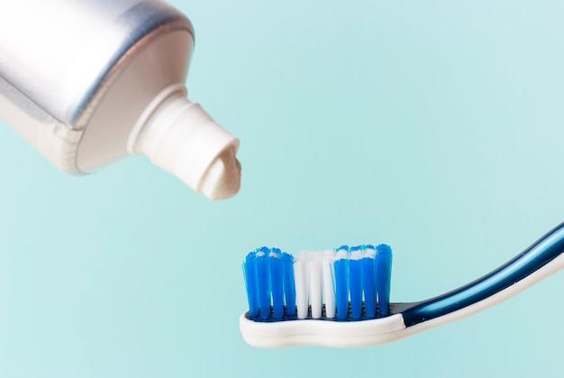Pasta de dientes en tubo y cepillo de dientes sobre fondo azul.