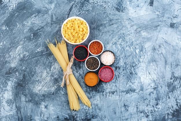 Pasta ditalini de vista superior en un tazón con espaguetis, especias sobre fondo de yeso gris. horizontal