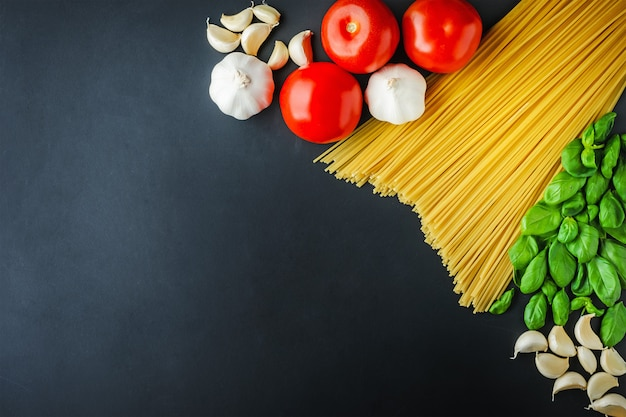 Pasta e ingredientes para cocinar sobre fondo oscuro con espacio de copia