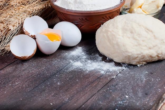 Pasta e ingredientes para hornear en la vieja mesa de madera.