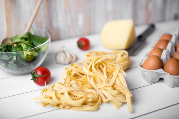 Pasta e ingredientes de tallarines crudos sobre mesa de madera