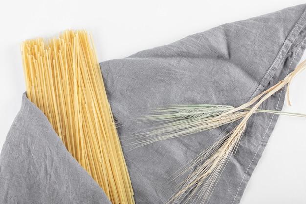 Pasta de espagueti sin cocer sobre mantel gris con trigo.