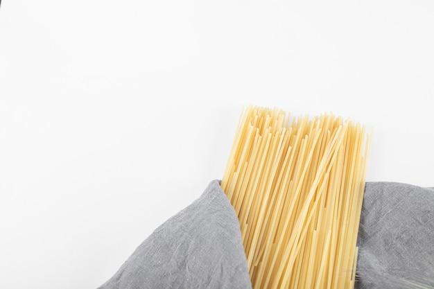 Pasta de espagueti sin cocer sobre mantel gris.