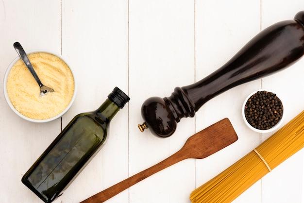 Pasta de espagueti cruda y su ingrediente con utensilio de cocina en mesa blanca