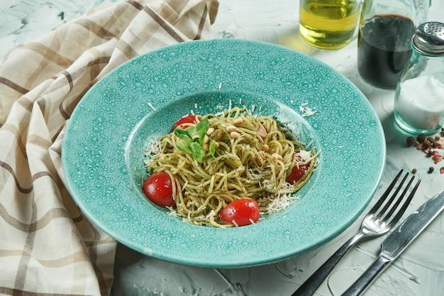 Pasta de espagueti italiana casera con salsa de pesto y tomates cherry, parmesano en un plato azul sobre un fondo beige. vista cercana