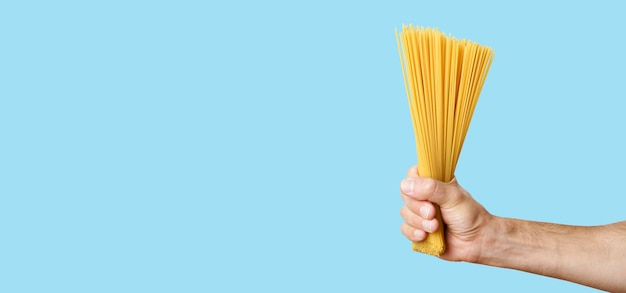 Pasta de espagueti en la mano sobre un fondo de banner en blanco espaguetis italianos crudos antes de cocinar y comer ...