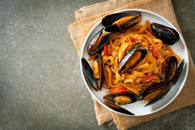 Pasta de espagueti con mejillones o almejas y salsa de tomate - estilo de comida italiana