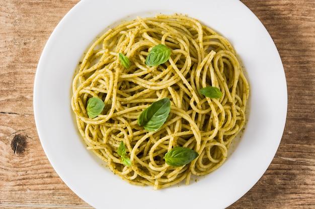 Pasta de espagueti con salsa de pesto en mesa de madera