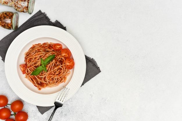 Pasta, espagueti con salsa de tomate y albahaca en plato blanco sobre fondo claro con espacio de copia
