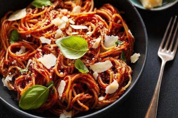 Pasta de espagueti con salsa de tomate, queso y albahaca servida en un bol.