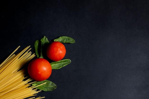 Pasta de espagueti, tomate y otros productos para cocinar en la vista superior de fondo oscuro. espacio para texto, vista superior