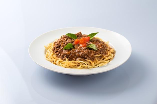 Pasta de espaguetis a la boloñesa con hojas de albahaca sobre fondo blanco.
