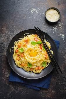 Pasta espaguetis carbonara con tocino, queso parmesano, yema de huevo y hojas de albahaca sobre superficie negra. plato tradicional italiano