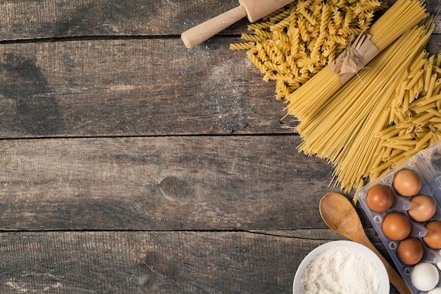Pasta de espaguetis con harina, huevo sobre madera vieja.