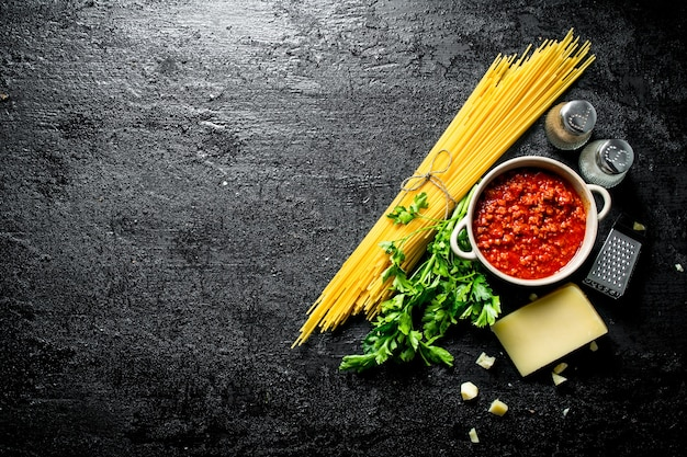 Pasta. espaguetis secos con salsa boloñesa, hierbas, tomate y queso. en rústico negro