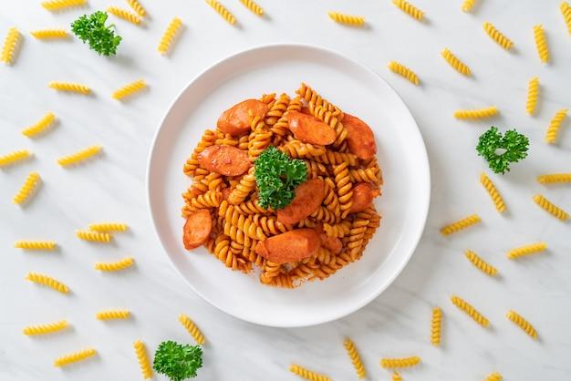 Pasta en espiral o spirali con salsa de tomate y salchicha, estilo italiano
