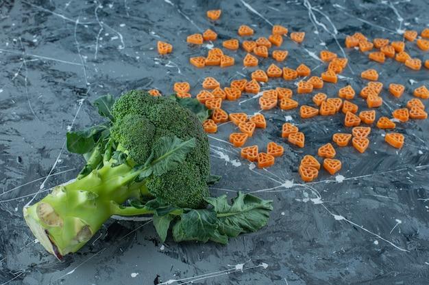 Pasta espolvoreada y brócoli fresco sobre la superficie de mármol
