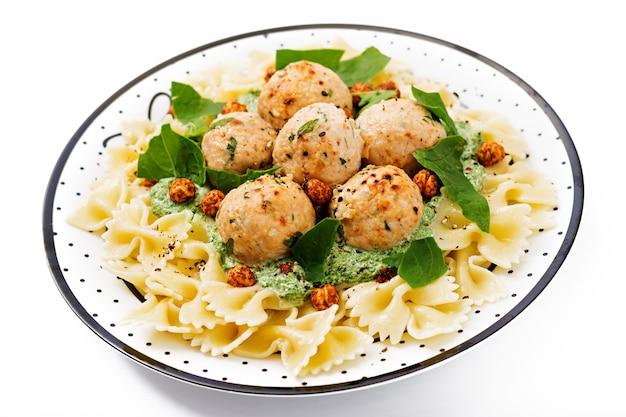 Pasta farfalle con albóndigas y salsa de espinacas con garbanzos fritos.