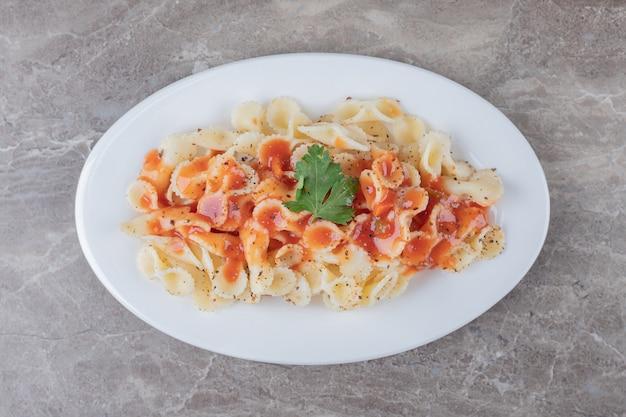 Pasta farfalle con boloñesa en el plato, sobre la superficie de mármol.