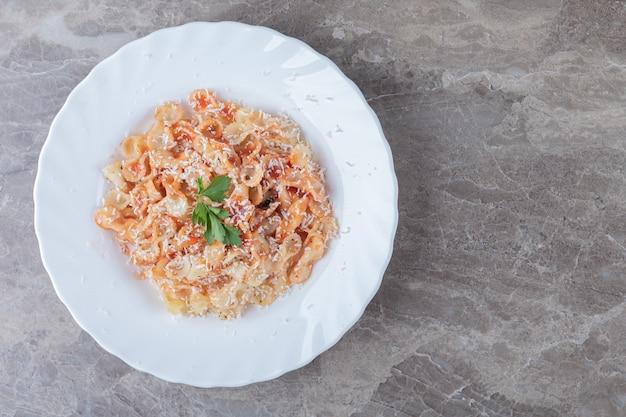 Pasta farfalle con boloñesa sobre el bol, sobre el mármol.