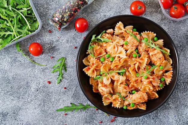 Pasta farfalle con filete de pollo, salsa de tomate y guisantes. cocina italiana. menú. vista superior. cena. endecha plana.