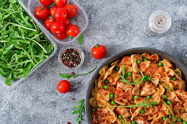 Pasta farfalle con filete de pollo, salsa de tomate y guisantes. comida hecha en casa. cocina italiana. endecha plana menú de comida. vista superior