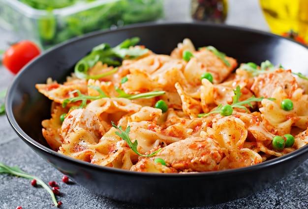 Pasta farfalle con filete de pollo, salsa de tomate y guisantes. menú