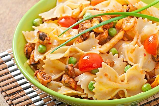 Pasta farfalle con mariscos, tomates cherry y guisantes