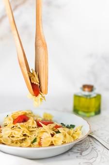 Pasta farfalle recogida con cuchara de madera y espátula del plato