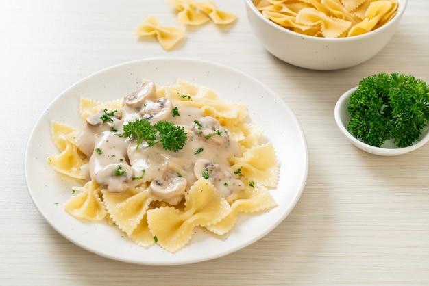 Pasta farfalle con salsa de crema blanca de champiñones - estilo de comida italiana