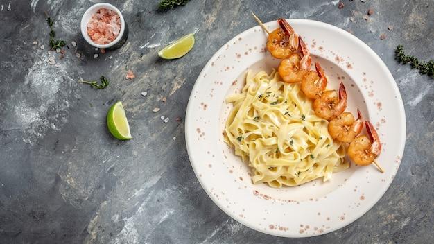Pasta fettuccine con langostinos o camarones, limón y ajo, fettuccine de pasta italiana. banner, lugar de receta de menú para texto, vista superior.