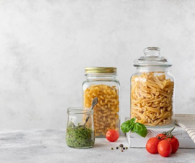 Pasta en frasco de vidrio y aceite de oliva en botella.