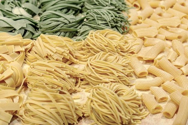 Pasta fresca cruda hecha en casa con espinacas y trigo en la mesa.