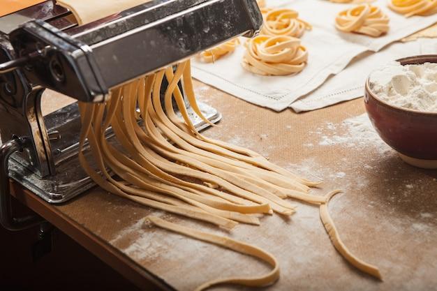 La pasta fresca y la máquina en la mesa de la cocina.