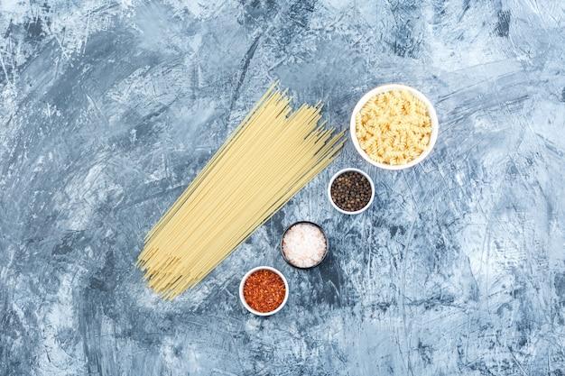 Pasta fusilli laicos plana en un tazón blanco con espaguetis, especias sobre fondo de yeso sucio. horizontal