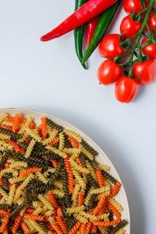 Pasta fusilli en un plato con tomates, pimientos planos sobre una mesa blanca