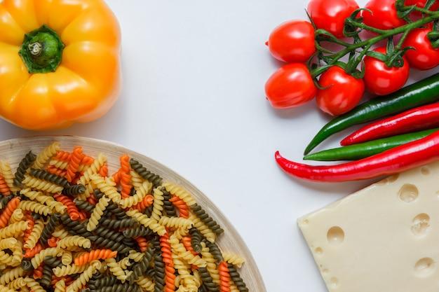 Pasta fusilli en un plato con tomates, pimientos, queso, ángulo de visión alta sobre una mesa blanca