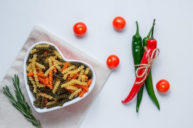 Pasta fusilli en un recipiente con pimientos, tomates, vista superior de la planta verde sobre la mesa de mantel blanco y doblado