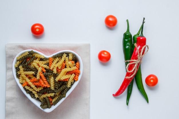 Pasta fusilli en un recipiente con pimientos, vista superior de tomates en mantel blanco y doblado