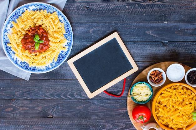 Pasta fusilli con salsa de tomate, tomate, cebolla, ajo, pimentón seco, aceitunas, pimiento y aceite de oliva.