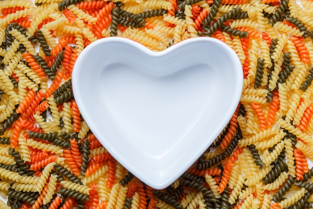 Pasta fusilli con un tazón en forma de corazón plano.